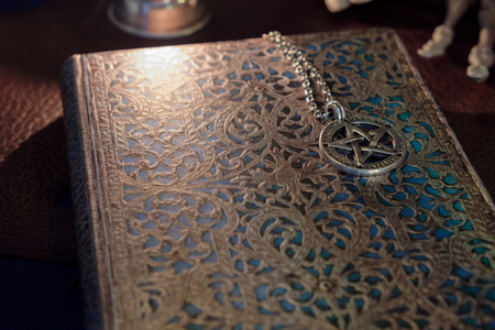 View of pentacle necklace on vintage book. Soft focus. Under candlelight.
