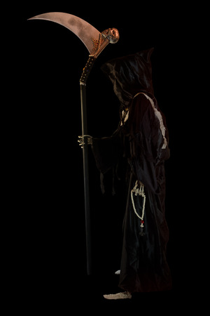 Hooded skeleton on black background. Grim Reaper, The Death. Stock Photo