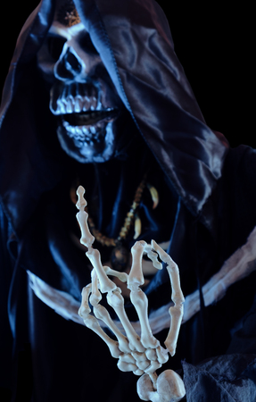 View of grim reaper show middle finger on black background. Grim Reaper, The Death. Shallow depth of field. 스톡 콘텐츠
