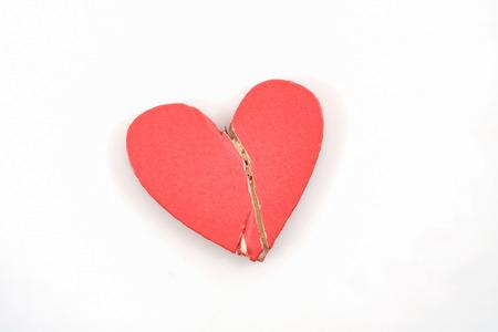 Broken red heart on white background.