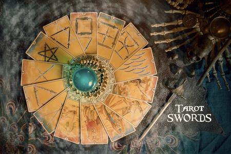 View of Tarot card (Minor arcana) and crystal ball on the table. Tarot of swords.