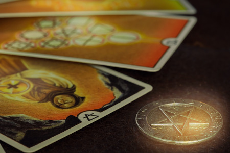 View of pentacle coin and Tarot card (Minor arcana) on the table. Dark tone. Stock Photo