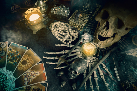 View of skull and Tarot card (Minor arcana) on the table. Dark tone. Stock Photo