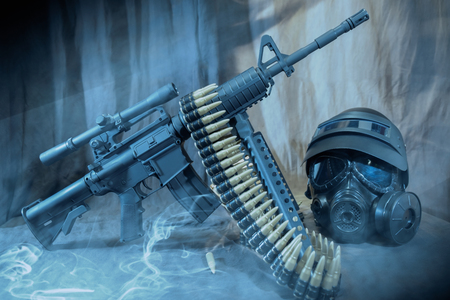 View of gas mask with helmet and machine gun on the table. Dark tone. Soft focus. Stock Photo