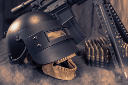 View of skull with helmet and machine gun on the table. Dark tone. Soft focus.