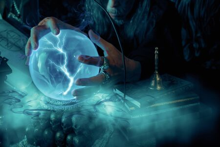 Close up crystal ball with light and wizards in dark room.