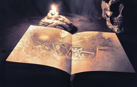 View of tarot book open on the table, under candlelight. The devil. Digital paint. Watercolor style.