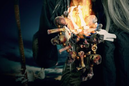Skull necklace with fire in devil hand. Digital retouch. 写真素材