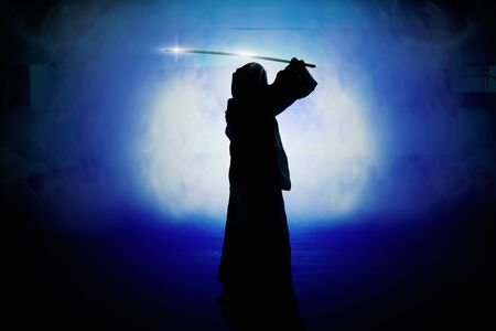 Silhouette of man in robe holding sword with smoke and light in parking lot.