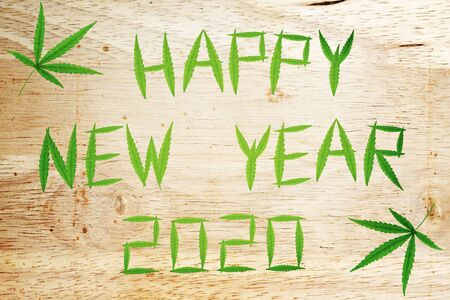View of marijuana leaf on wood background. Happy New Year 2020.