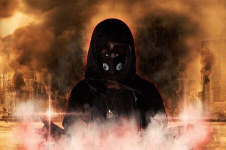 Portrait of hooded man with mask standing in the smoke on burning city background. Judgment day.3D illustration.