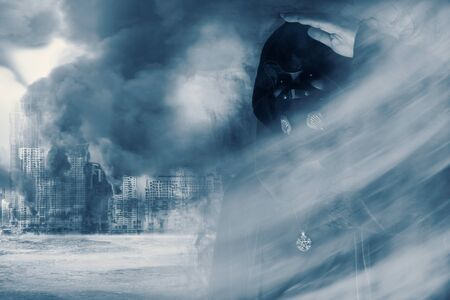 View of hooded man with mask standing in the smoke on burning city background. Judgment day. 3D illustration.