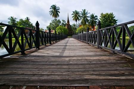wooden bridge leading to Buddha stupa in temple ruins of sukothai historic park thailand Stock Photo