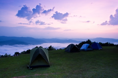 Tent  on top of a mountain in the early morning sunrise