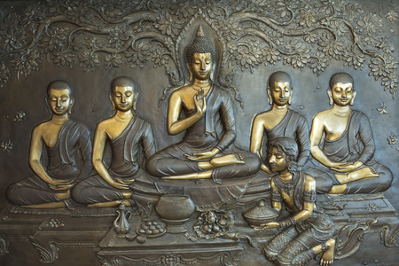 Buddha life scenes on carved metal at the temple in Thailand