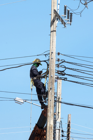 Electrician connects wires on a pole 版權商用圖片