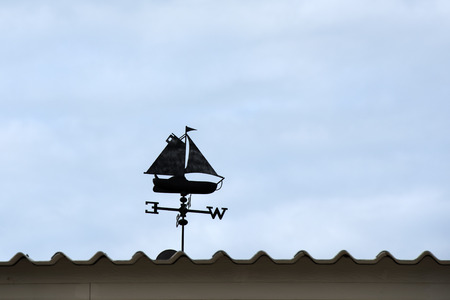 Weather vane on the roof against blue sky