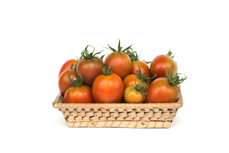 Group of tomatoes in a wicker basket Stock Photo