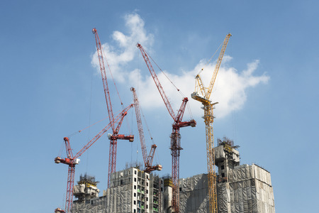 Group of construction crane on workplace against blue sky background Stock Photo