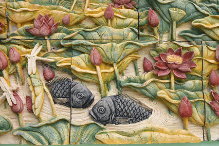 Stone carvings of fishes and beautiful flower on temple wall in Thailand