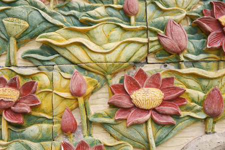 Stone carvings of beautiful flower on temple wall in Thailand