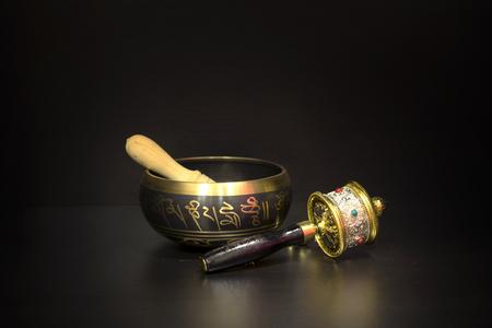 Tibetan mini mantra  Om mani padme hum writing on small singing bowl with prayer wheels