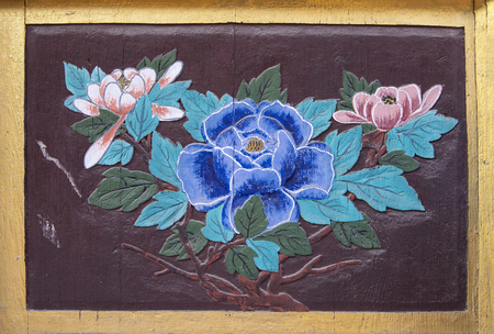 Pattern of flower carved on Wooden door decorations in a buddhist temple in South Korea.