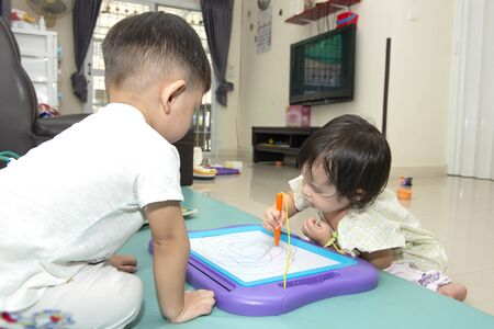 little girl and little boy playing with magnetic drawing board on the floor Imagens