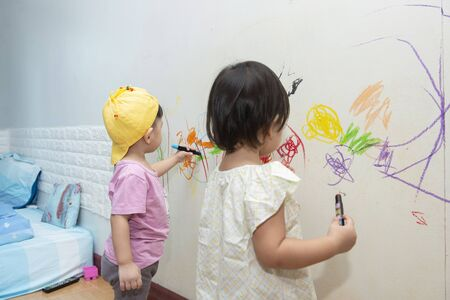 little baby  boy and girl drawing with crayon color on the wall