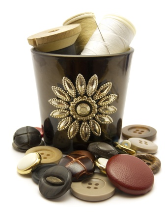 Close-up of sewing items in a pot surrounded by buttons isolated in white photo