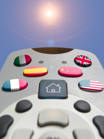 Remote Control with flag buttons pointing at sun in blue sky photo