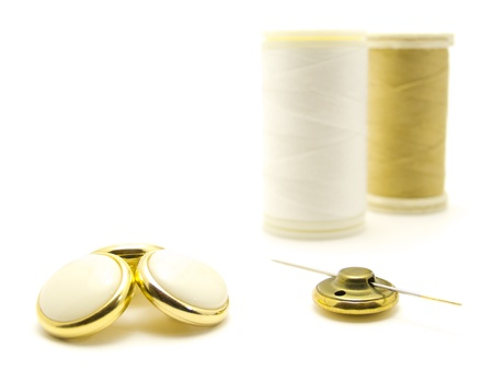 Two spools, four buttons and one needle Stock Photo - 9830918