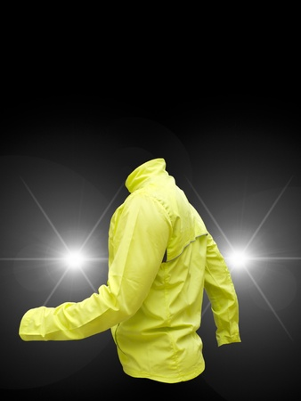 warning vest: Yellow fluorescent vest with car headlights on black background Stock Photo