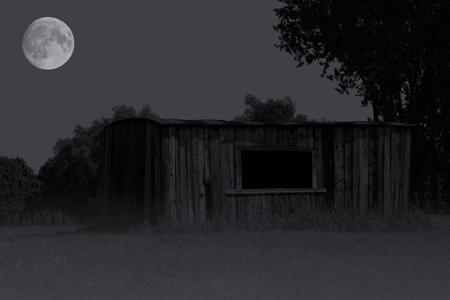 Mysterieuze schuur in mist met bomen en heldere volle maan op achtergrond