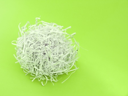 Shredded paper ball on green background photo