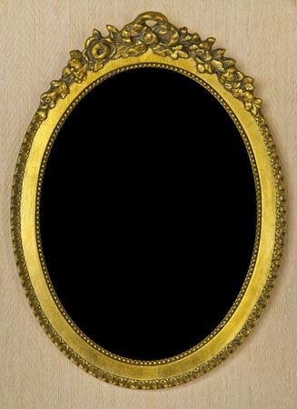 Round golden antique frame on wall photo