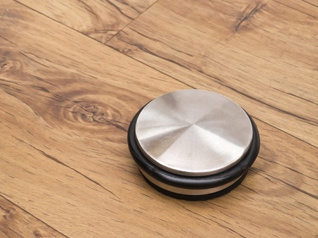 Door stop on wooden laminate parquet floor photo