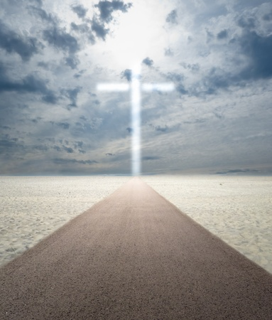 footprints in the sand: Road in sand leading to glowing cross out of sky Stock Photo