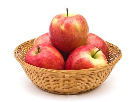 canastas con frutas: Las manzanas rojas en el cesto de mimbre en blanco