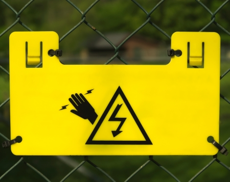 Yellow electric fence sign closeup Stock Photo - 13659589