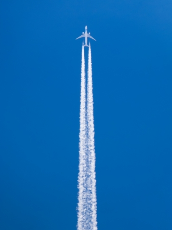Closeup on airplane contrail against clear blue sky photo