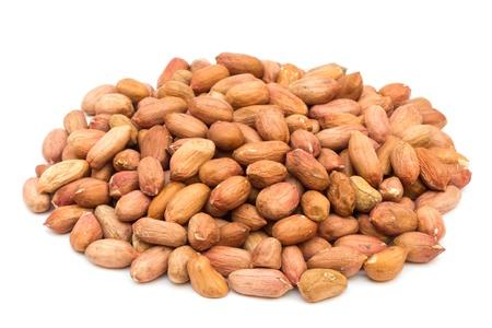 unpeeled: Unpeeled peanuts pile on white