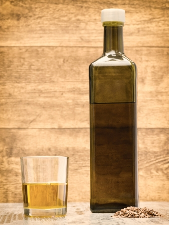 flax seed oil: Flax seed oil bottle with glass on wooden background Stock Photo