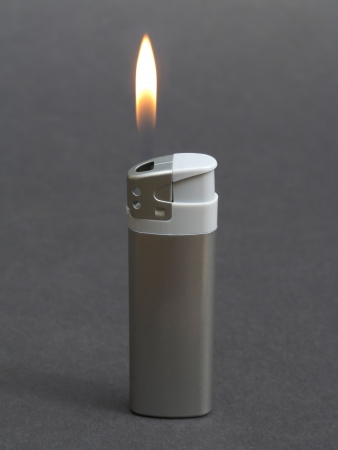 gas lighter: Lit silver lighter on gray background