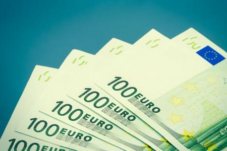 Five hundred euro bills on blue background with vignette photo