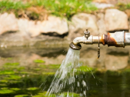 Rusty water tap flowing in pond photo