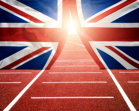 Olympics London concept with sun shining trough flag curtains on running track photo