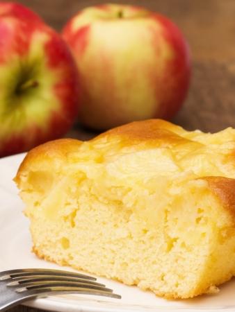 porcion de torta: Tarta de manzana en un plato con manzanas en el fondo Foto de archivo