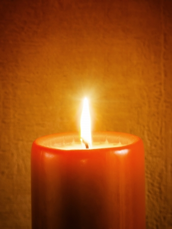 warmth: Burning holiday candle on brown wallpaper with vignette Stock Photo