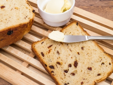 Homemade raisin bread on cutting board with butter photo